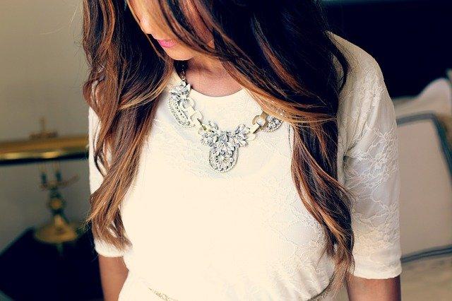 Hnedovlasá žena v bielej blúzke a strieborným náhrdelníkom.jpg