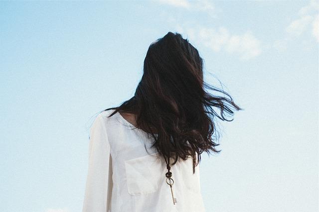 Žena v bielej tunike s výrazným šperkom na krku, ktorej vejú vlasy vo vetre.jpg