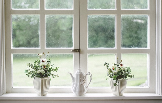 Porcelánový čajník a vázy na parapetnej doske pod dreveným oknom.jpg
