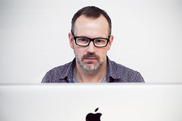 Muž v dioptrických okuliaroch pozerá prekvapene na monitor počítača
