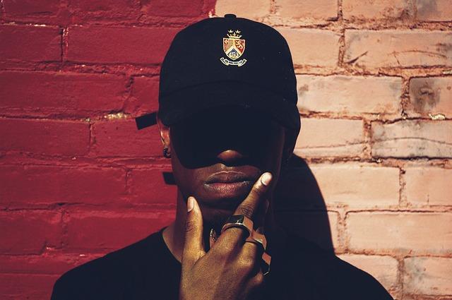 Muž s čiernou šiltovkou v tvári stojí pri tehlovej stene a premýšľa