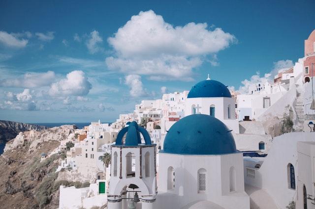 Biele budovy s modrými kupolovitými strechami postavené na útese nad morom