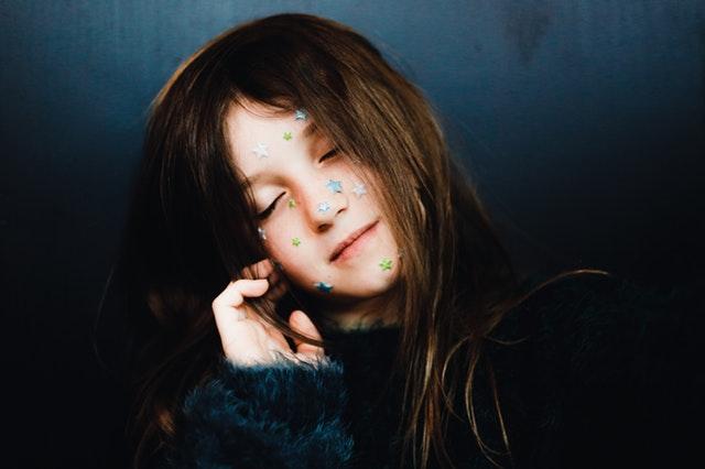 Dievča s hviezdičkami na tvári má zatvorené oči a sníva