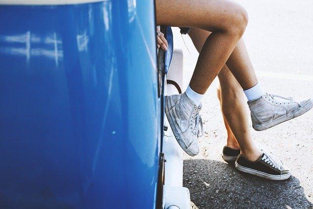 Ľudia sedia v modrej dodávke s vystrčenými nohami v teniskách.jpg