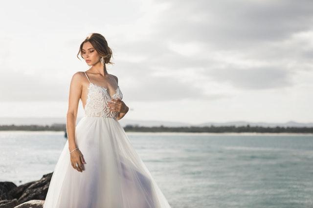 Žena – nevesta v svadobných šatách stojí na brehu jazera.jpg