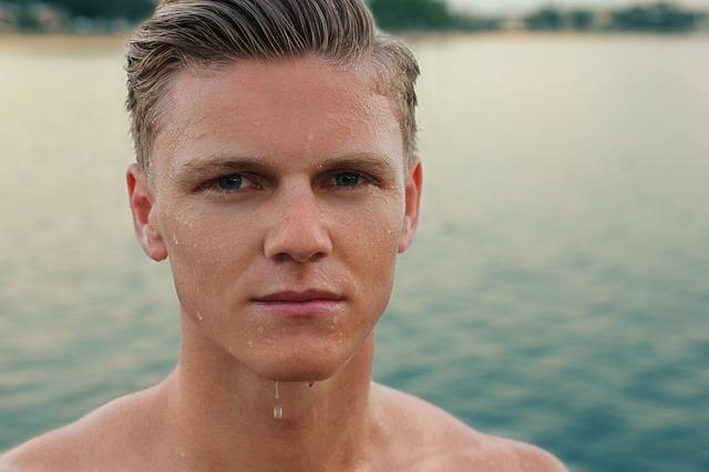 Mladý muž so svetlými vlasmi má mokrú tvár a stojí pri vode.jpg